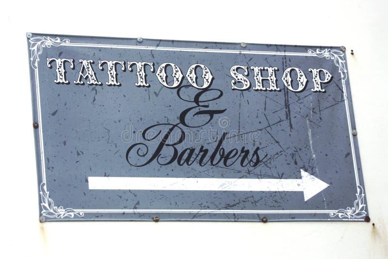 Tatúe la tienda y los peluqueros firman en una pared blanca imagenes de archivo