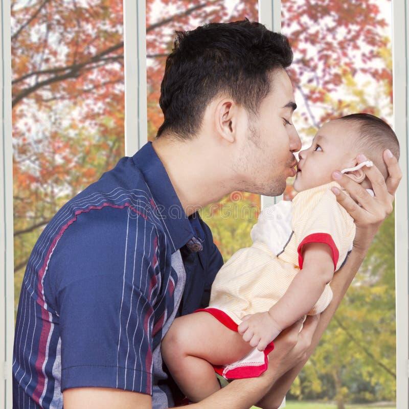 Tata buziaka męski dziecko w domu obrazy stock