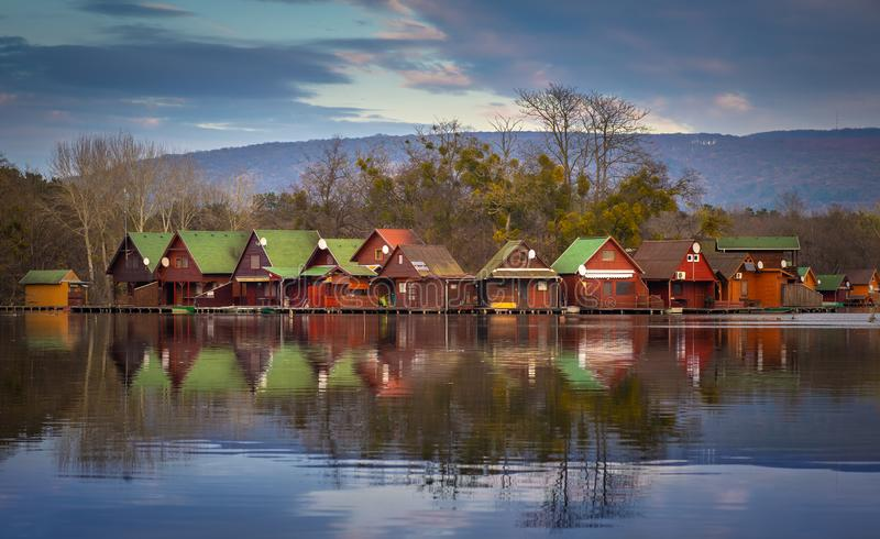 Tata, Hungary - Fishing cottages by the lake Derito on a small island at sunset with reflections stock image