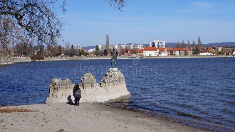 Tata Hungary 03 04 2017 turistas fotografa a estátua sagrado do George santamente no lago Tata fotografia de stock