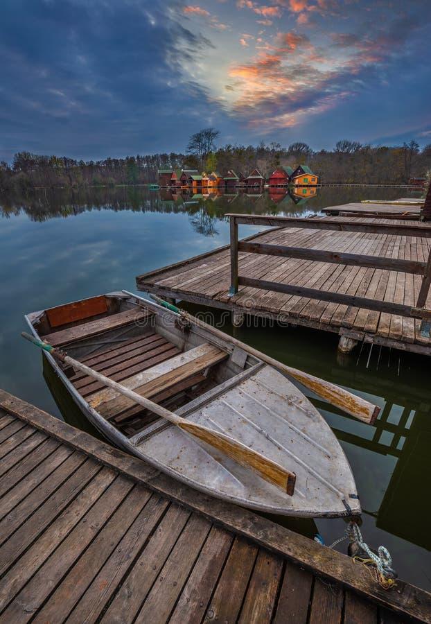 Tata, Hungría - barco de pesca por el lago Derito Derito con a las cabañas pesqueras de madera imágenes de archivo libres de regalías