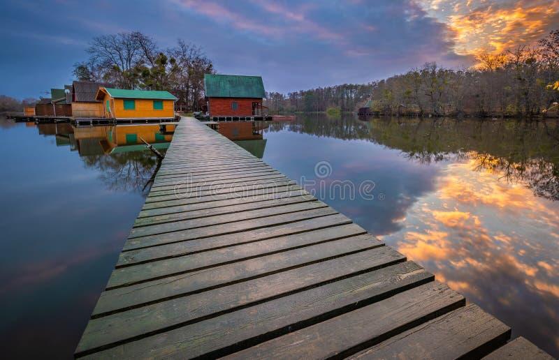 Tata, Hungria - casas de campo da pesca na ilha pequena no lago Darito Derito no por do sol com céu de surpresa foto de stock