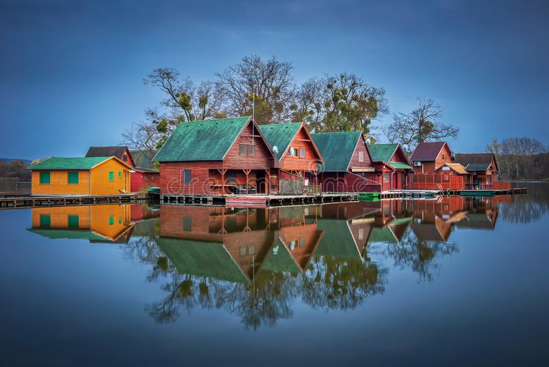 Tata, Hungria - casas de campo de pesca de madeira em uma ilha pequena no lago Derito Derito na hora azul fotos de stock royalty free
