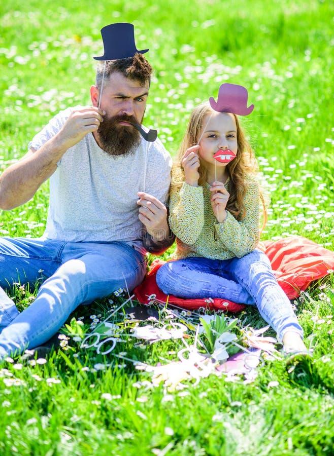 Tata i córka siedzimy na trawie przy grassplot, zielony tło Dziecko i ojciec pozuje z odgórnym kapeluszem, wargami i fajczaną fot zdjęcia stock