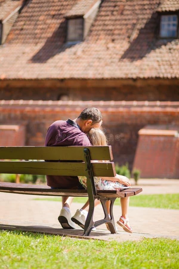 Tata i córka siedzimy przytulenie na ławce w miasto parku fotografia royalty free