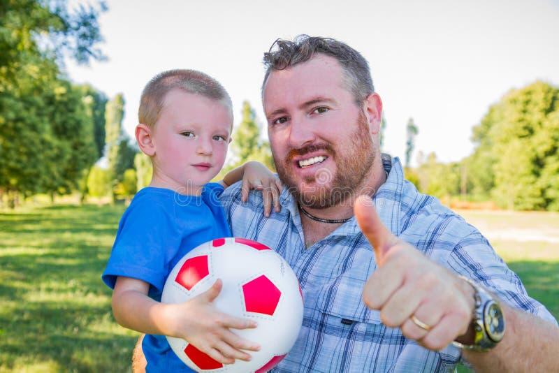 Tata i chłopiec sztuka z piłką fotografia stock