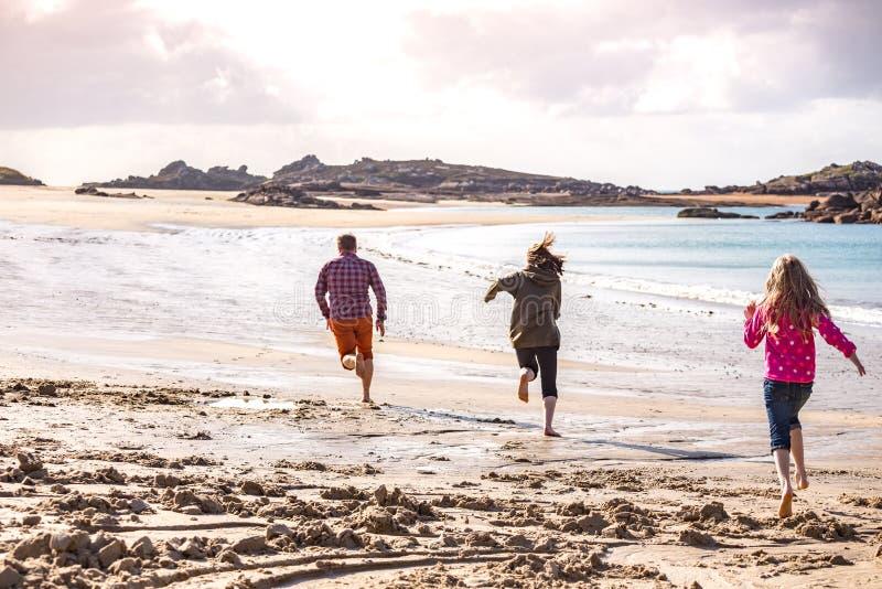 Tata i dwa córki biega wzdłuż plaży fotografia royalty free