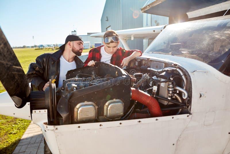Tata i jego żartujemy sprawdzać małego śmigłowego samolot na zewnątrz samolotu hangaru obraz royalty free