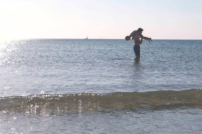 Tata i syn bawić się wpólnie w wodzie morskiej na zmierzchu Pływać w morzu obrazy royalty free