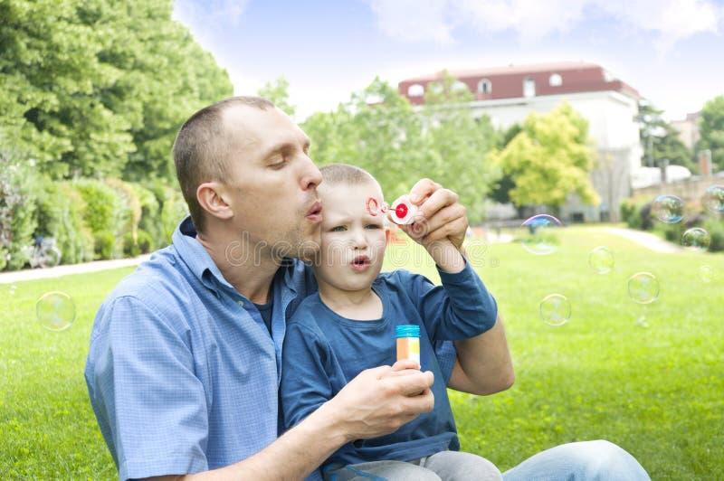 Tata i syn dmucha mydlanych bąble fotografia stock
