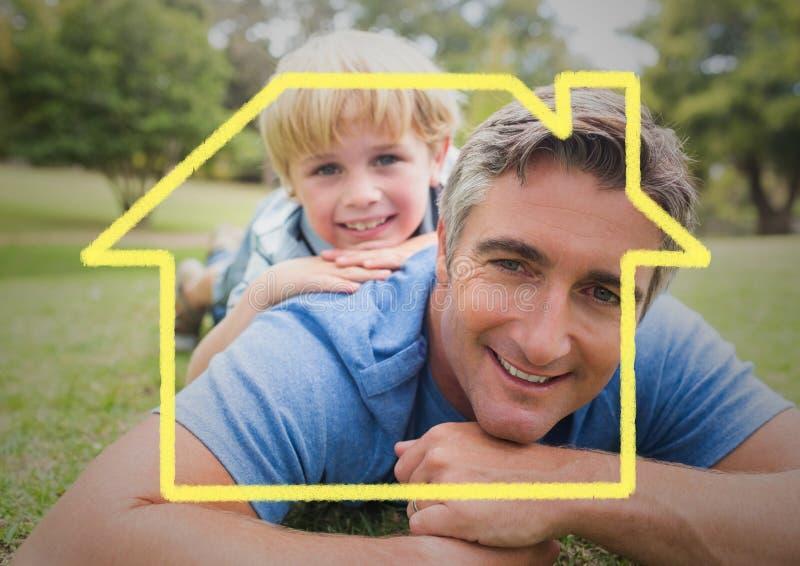 Tata i syn kłaść w parku przeciw domowemu konturowi w tle obrazy stock