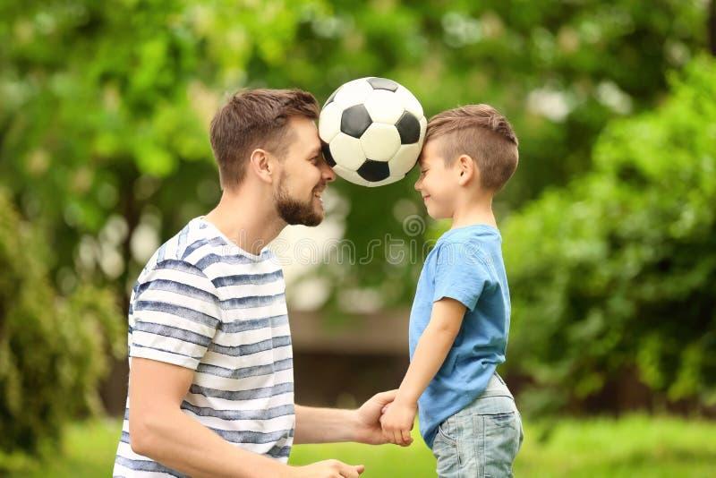 Tata i syn z piłki nożnej piłką zdjęcie stock
