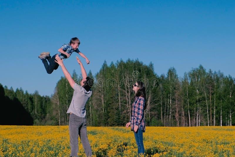 Tata rzuca jego syna w powietrzu i macierzystych stojaków następnie, Rodzinny spacer na polu z kolorem żółtym kwitnie blisko lasu obrazy royalty free