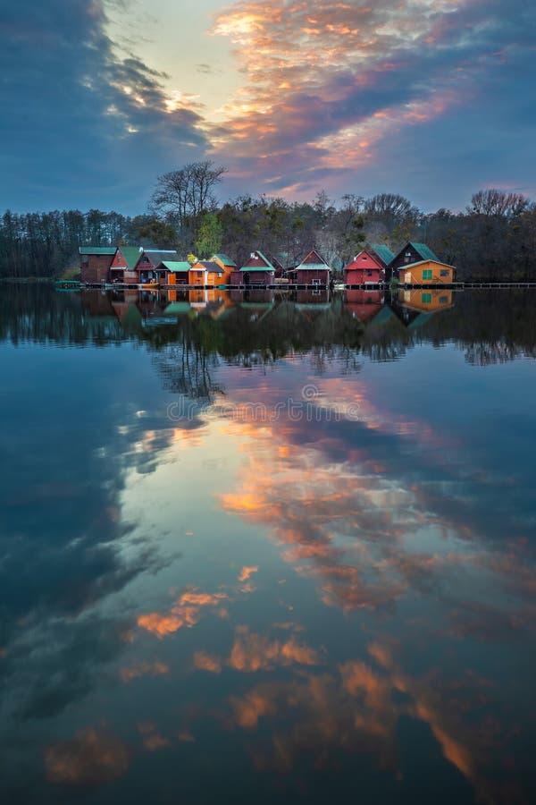 Tata, Ungarn - schöner Sonnenuntergang über hölzernen Fischereihäuschen auf einer kleinen Insel am See Derito lizenzfreie stockfotos
