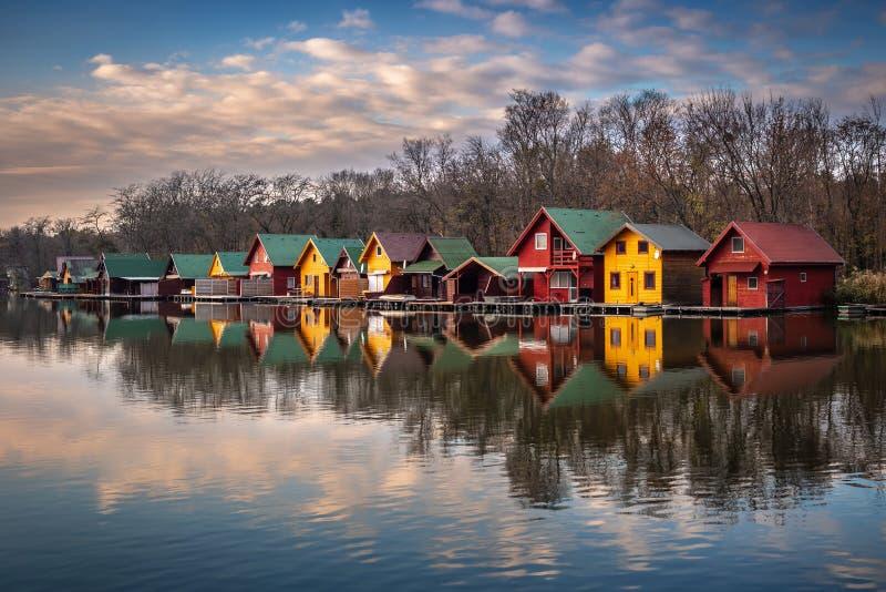 Tata Ungern - fiskestugor vid sjön Derito Derito till på solnedgången med reflexioner och färgglad himmel arkivbild