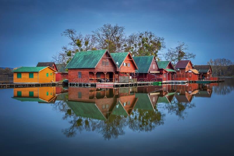 Tata, Węgry - Drewniane połów chałupy na małej wyspie przy jeziornym Derito Derito przy błękitna godzina zdjęcia royalty free