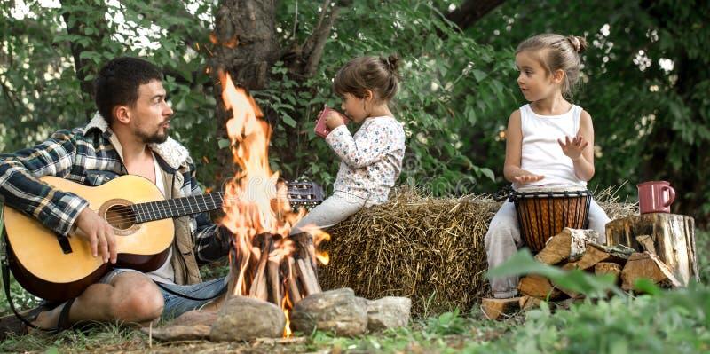 Tata z córkami odpoczywa w campingu na naturze obraz royalty free