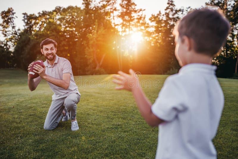 Tata z synem bawić się futbol amerykańskiego obraz royalty free