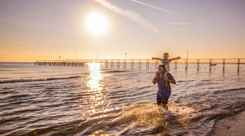 Tata z synem na jego brać na swoje barki spacery w wodzie przy morzem zdjęcia royalty free
