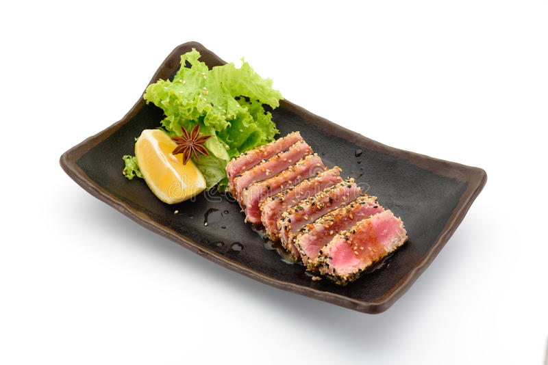 Tataki & x28;tuna fillet& x29; on a black plate. On white background stock photos