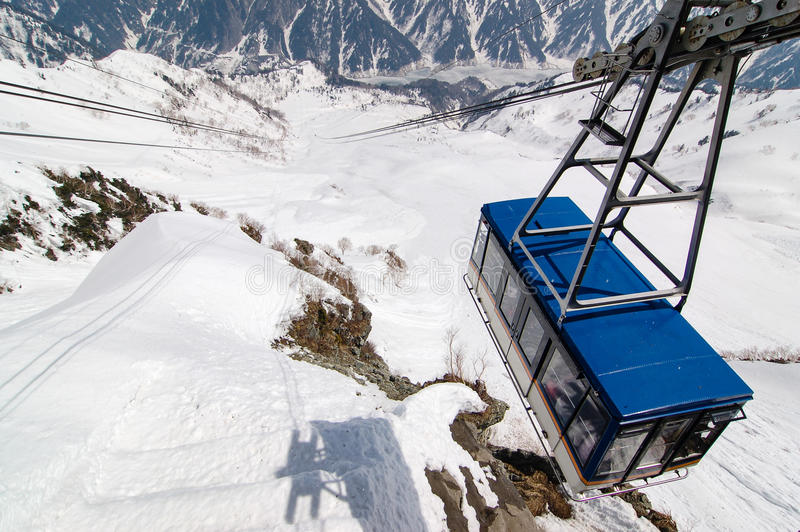 Tateyama Ropeway above snowy valley with shadow. Tateyama Ropeway in bright blue roof moving up and down above the valley with fully snow on a sunny day is one royalty free stock photography