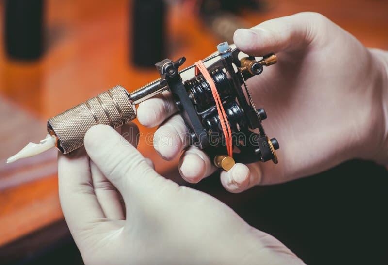 Tatoegeringskunstenaar in witte handschoenen die klaar om een tatoegering te doen worden stock afbeeldingen