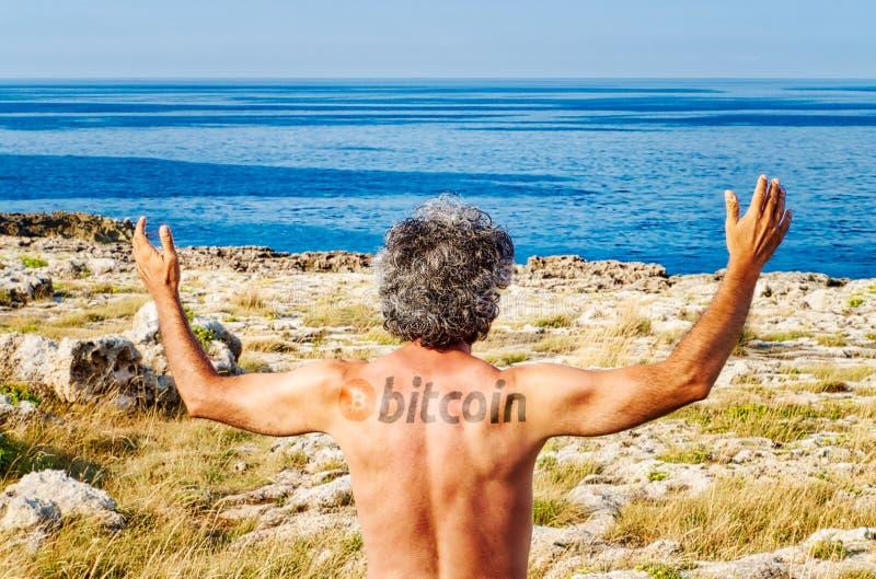 Tatoo de Bitcoin sur l'homme soulevant des mains photographie stock