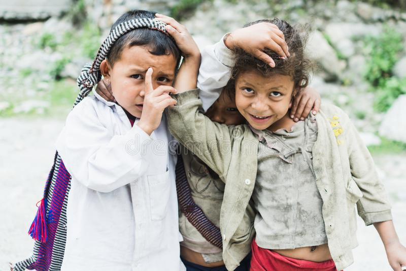 TATOPANI, НЕПАЛ - МАЙ 2015: портрет 3 детей непальца обнимая один другого стоковые фото