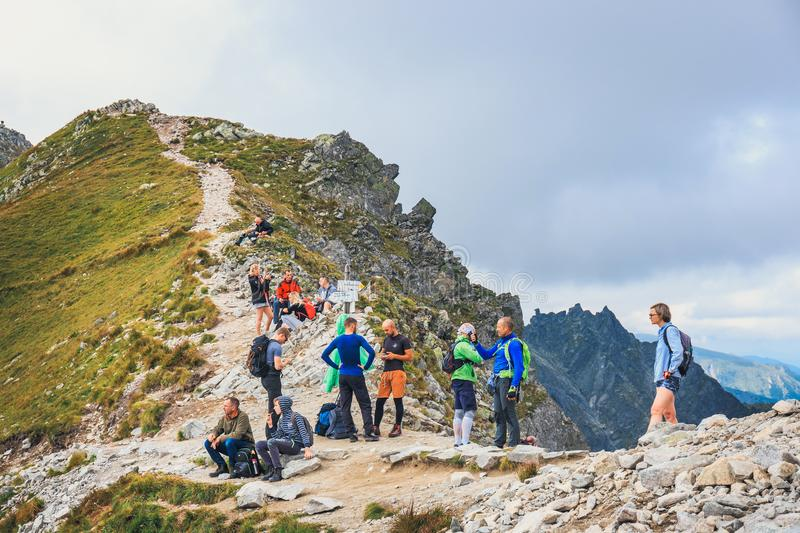 Unidentified group of hikers resting and exhausted at Krzyzne Pass in High Tatra Mountai. Tatra Mountains, Poland, August 14, 2017: Unidentified group of hikers royalty free stock photos