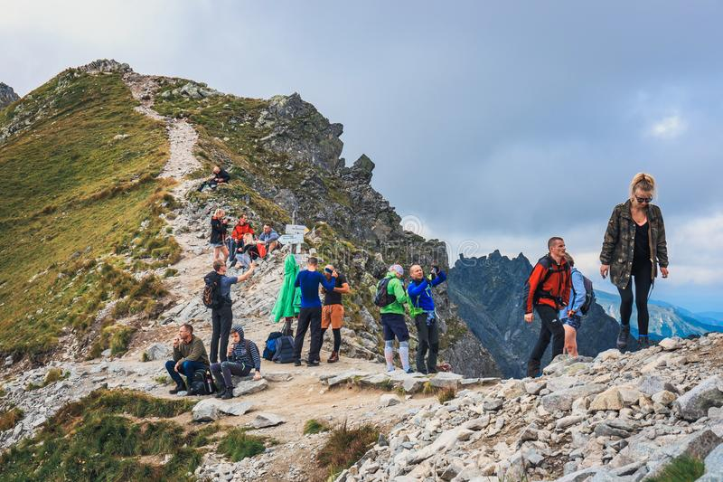 Unidentified group of hikers resting and exhausted at Krzyzne Pass in High Tatra Mountai. Tatra Mountains, Poland, August 14, 2017: Unidentified group of hikers stock photos