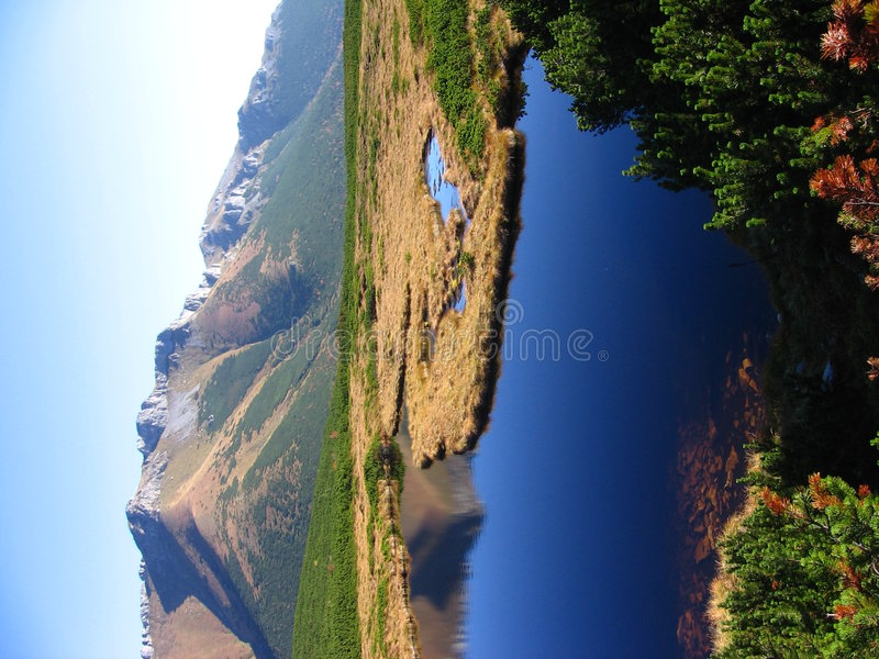 Tatry - mountain lake. Hills with prodtruding dolomite cliffs, reflecting in calm surface of mountain lake. Belianske Tatry mountains, Slovakia. Protected stock photos