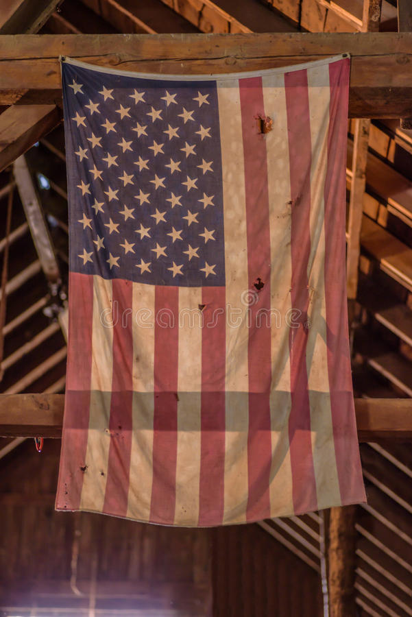 Tattered and faded American flag hanging in old barn royalty free stock photos