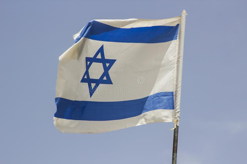 A tattered Israeli Flage aloft in a stiff breeze against a blue sky at the Banais Nature Reserve in the Golan Heights Israel. A tattered Israeli Flage aloft in a royalty free stock photo