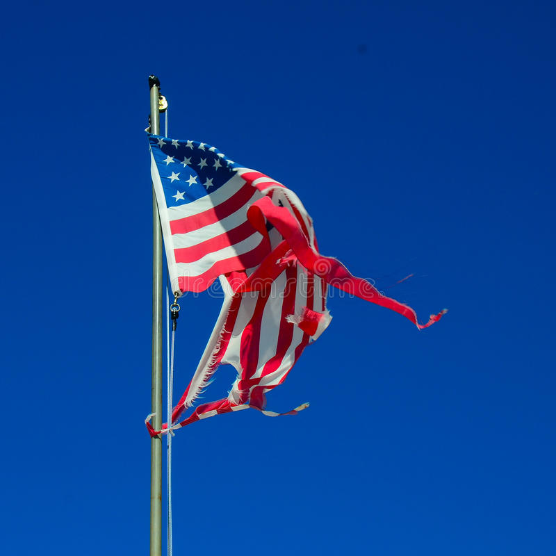 Torn American flag. Worn shredded American flag flapping in the wind royalty free stock image