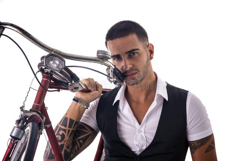 Tattoed elegante mens die zijn fiets houden stock afbeelding