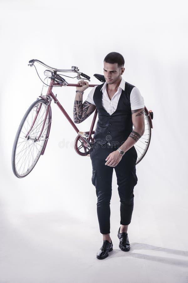 Tattoed elegante mens die zijn fiets houden stock fotografie