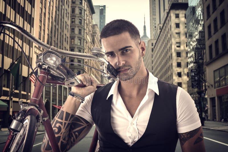 Tattoed elegante mens die zijn fiets houden stock foto