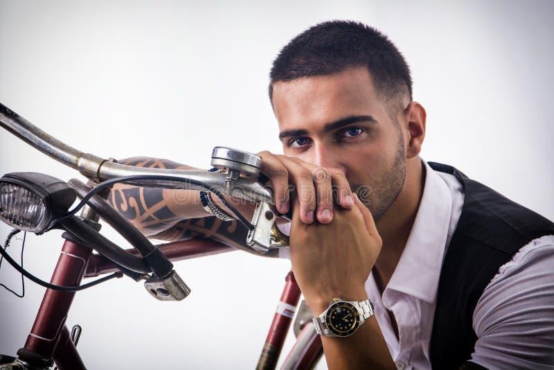 Tattoed het elegante mens cirkelen op fiets stock fotografie