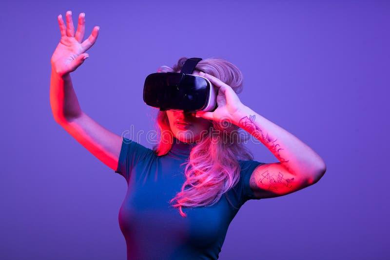 Tattoed sexig kvinna som bär en huvuduppsättning för virtuell verklighet VR fotografering för bildbyråer