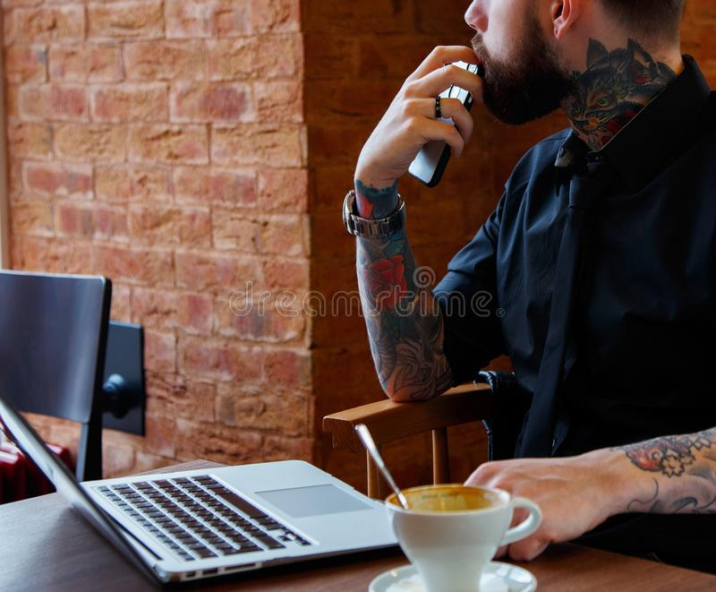 Tattoemens met baard en laptop stock afbeelding