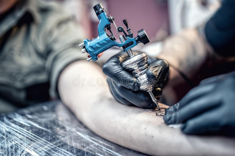 Tattoo artist drawing on client with special tools stock photos