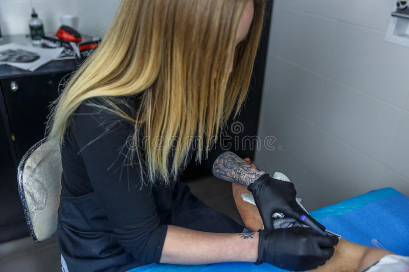 A tattoo artist draws the outline of a tattoo on a boy`s arm. A tattoo artist girl draws the outline of a tattoo on a boy`s arm stock images