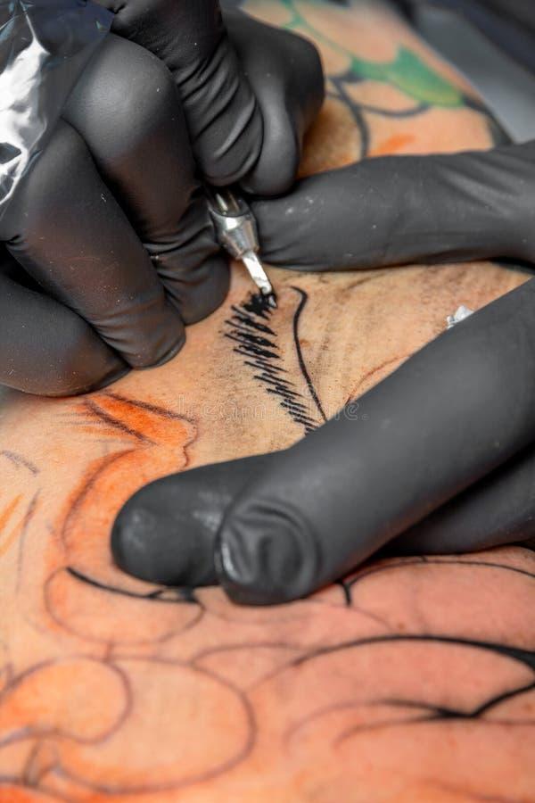 Tattoo artist at work stock photos