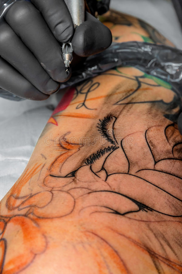 Tattoo artist at work royalty free stock image