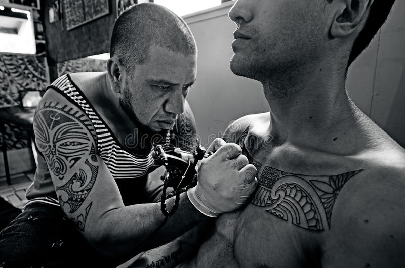 Tattoo Artwork. Pacific Island male tattoo artist draws a design on a chest of a young men client. real people 2 adult in tattoo studio. (BW royalty free stock images