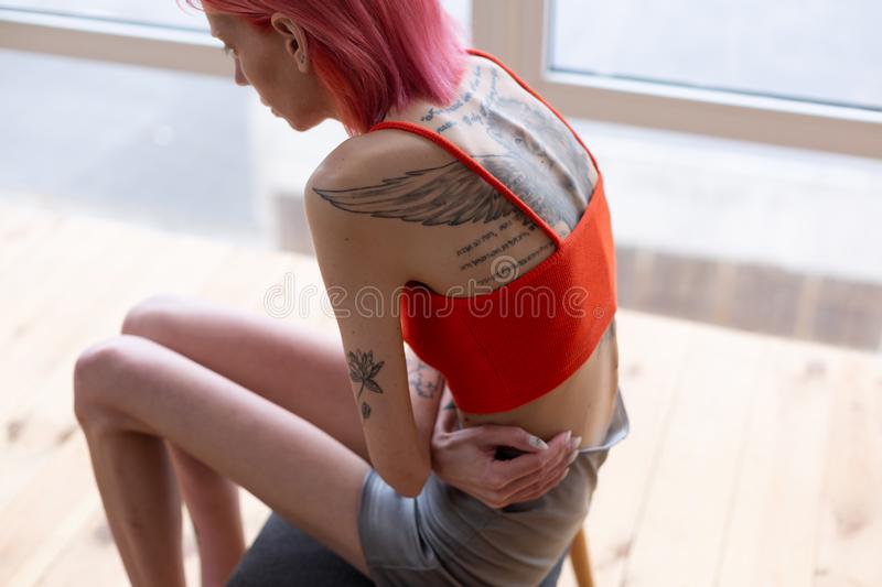 Slim woman with big tattoo on back suffering from pain. Tattoo on back. Slim red-haired anorexic woman with big tattoo on back suffering from pain royalty free stock image