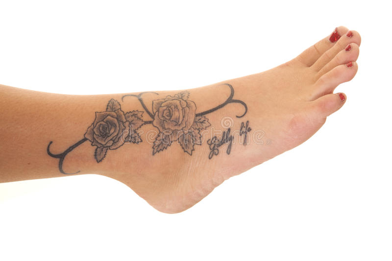 Tattoo close rose foot. A woman has a rose tattoo on her foot stock photo