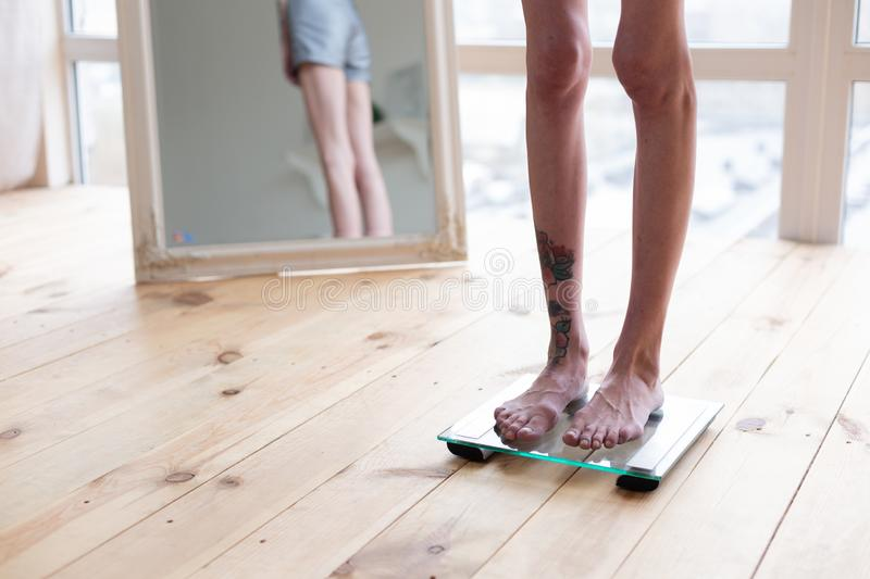 Skinny woman with tattoo on leg standing on weight scales royalty free stock images
