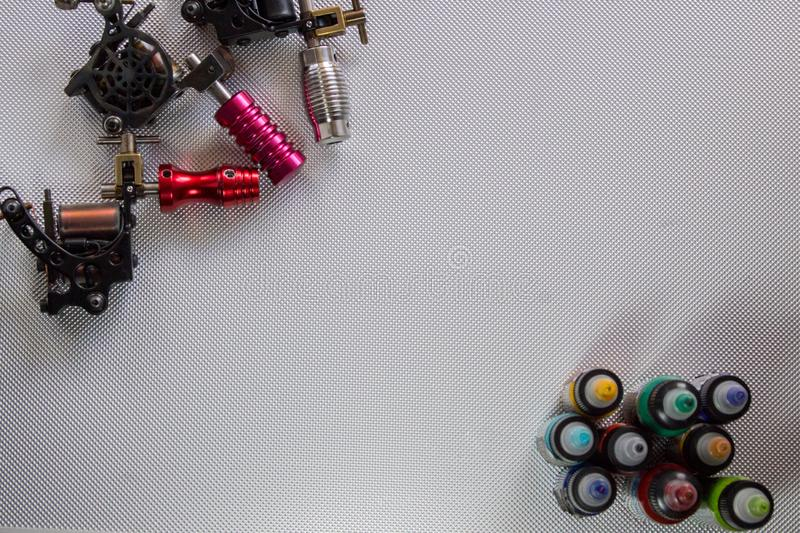 Tattoo machine and row of colored inks in plastic bottles stock photos