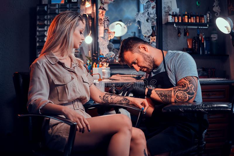 Tattoo master is creating new tattoo for customer royalty free stock image